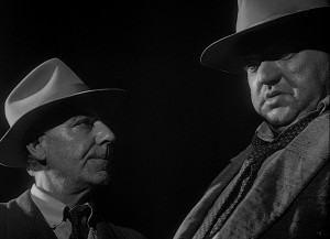 Partners in betrayal:  Menzies (Joseph Calleia) and Quinlan.